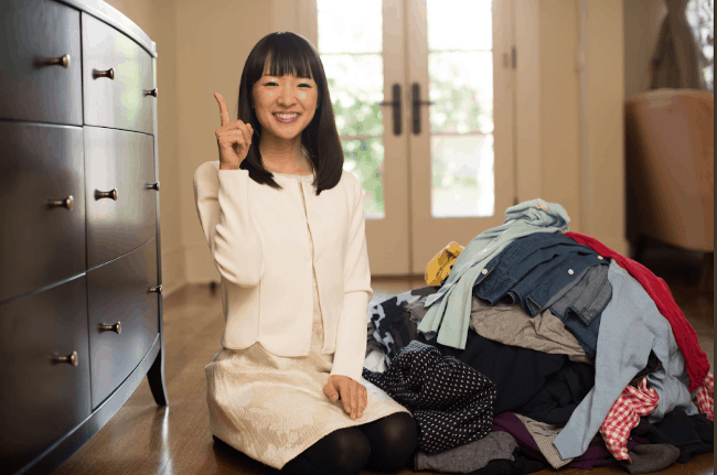 A woman kneeling on the floor next o a pile of clothes.