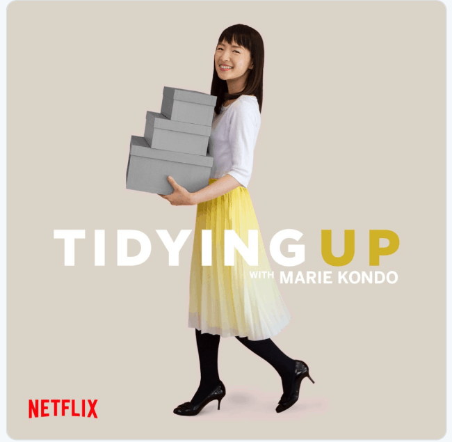A woman carrying  three neatly stacked boxes.