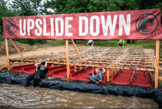 People crawling under a floating obstacle course exercise.