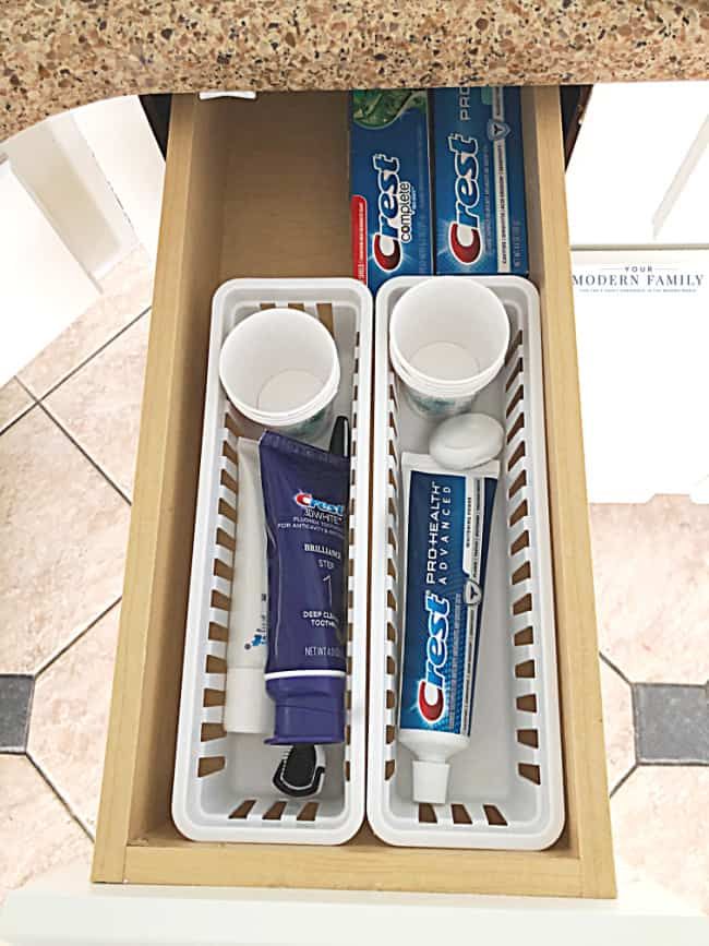 A close up of an open drawer with two plastic storage containers of Crest tooth brush.