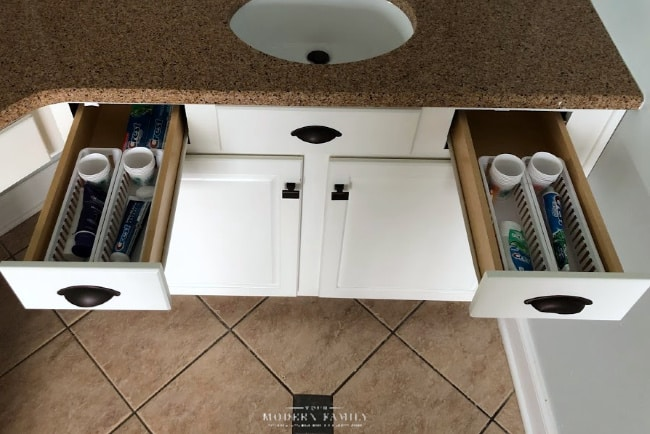 A picture of a bathroom counter with two drawers open with tooth paste and brushes in the drawer.