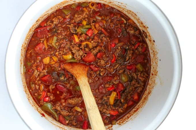 A large pot of chili with a wooden spoon.