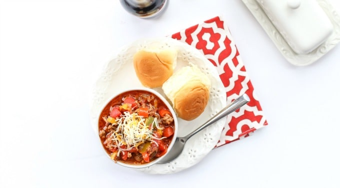 A bowl of chili on a plate with two rolls beside it.