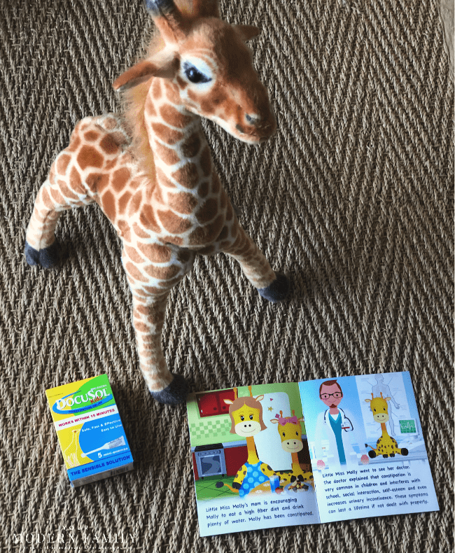 A toy giraffe standing beside a book and a box of Docusol for kids.