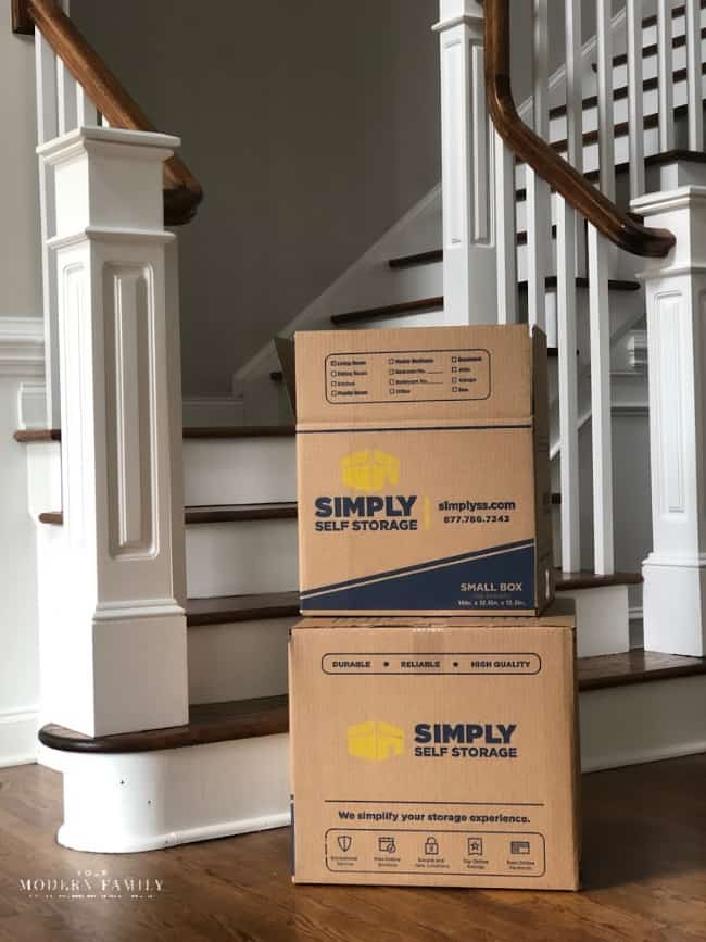 Boxes piled up on a wooden floor with stairs behind them.