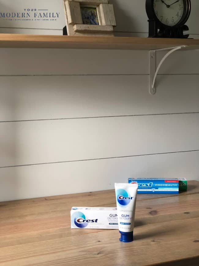 A tube of Crest Detoxify sitting on a wooden table.