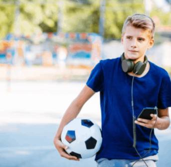 A little boy wearing a blue shirt holding a soccer ball and a cell phone.