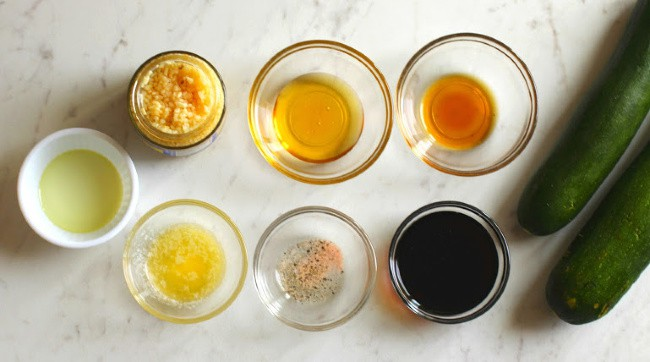 Six glass bowls with a variety of liquid and powder ingredients in them.