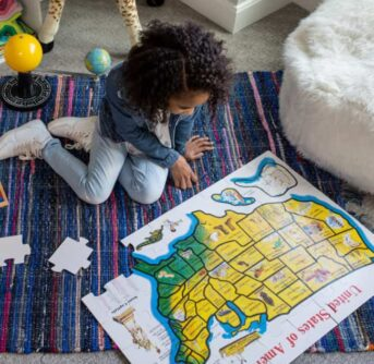 A little girl sitting on the floor building a puzzle.