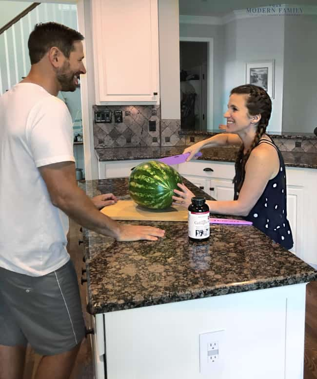 Two people standing at a kitchen counter preparing food.