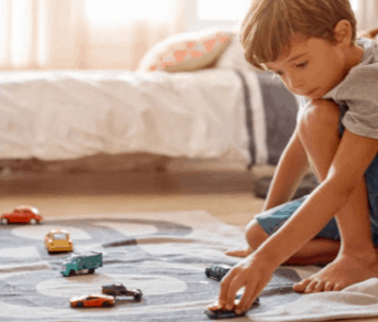 A small child playing cars on the floor.