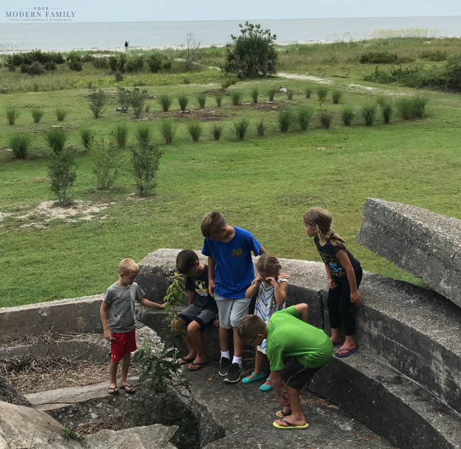 A group of kids that are standing on cement steps overlooking a grass field.