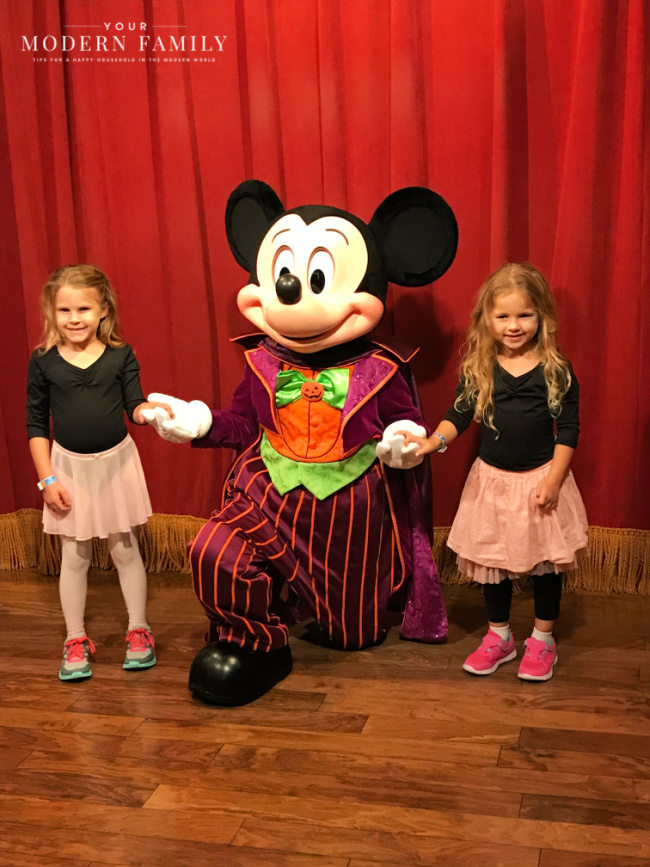 Two girls holding Mickey Mouse\'s hands.