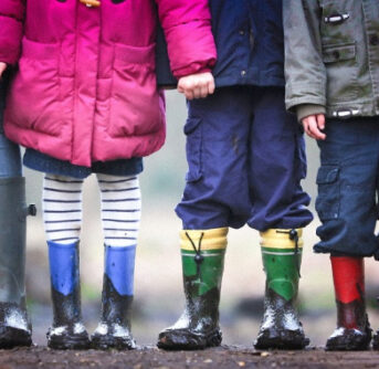 A group of kids posing for the camera wearing rain boots.