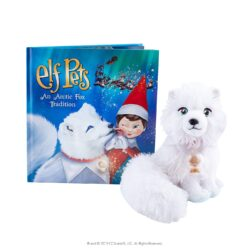 A close up of a stuffed animal in front of a Christmas book.