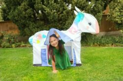A girl kneeling in front of a Unicorn tent.
