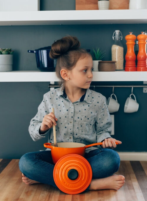 A small child sitting on a table with a pot and wooden spoon.