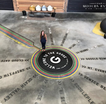 A lady standing on a floor with words on the floor.