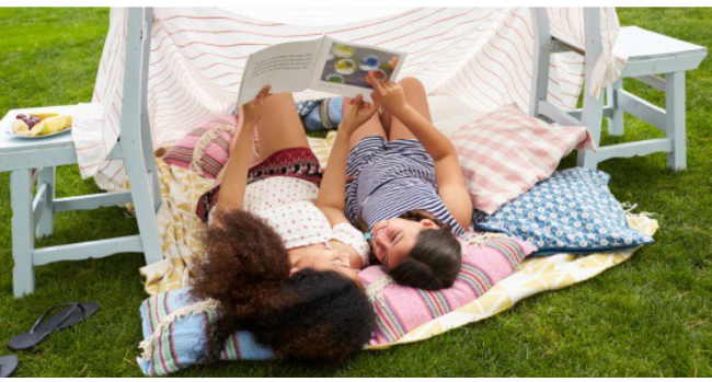 Two girls lying on a blanket reading a book in the grass.