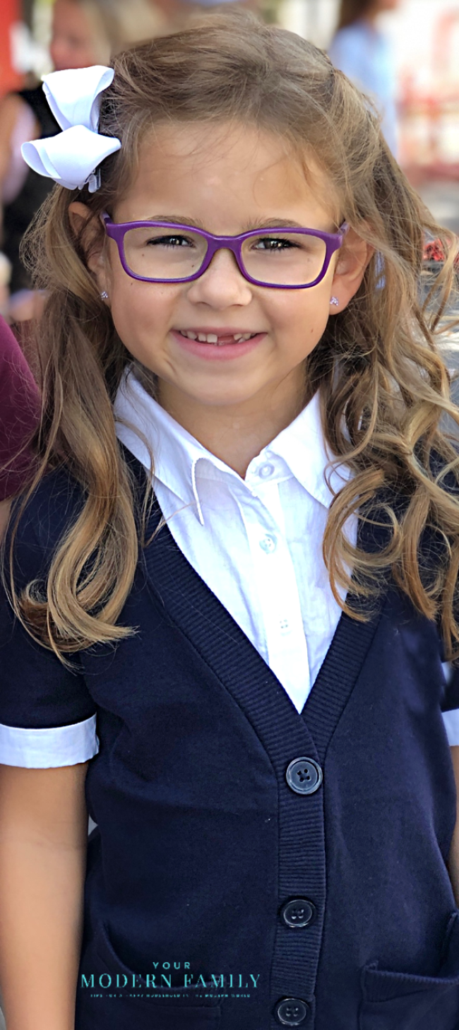 A girl wearing glasses and smiling at the camera