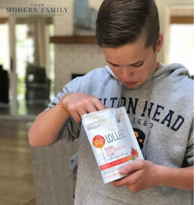A boy opening a bag of Lolleez lollipops.