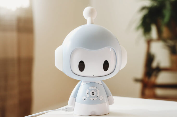A white robot toy sitting on a table.
