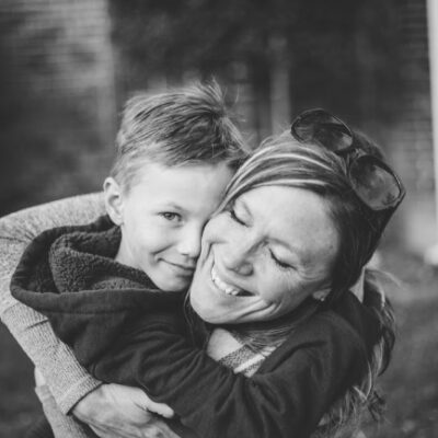 A lady and a boy hugging.