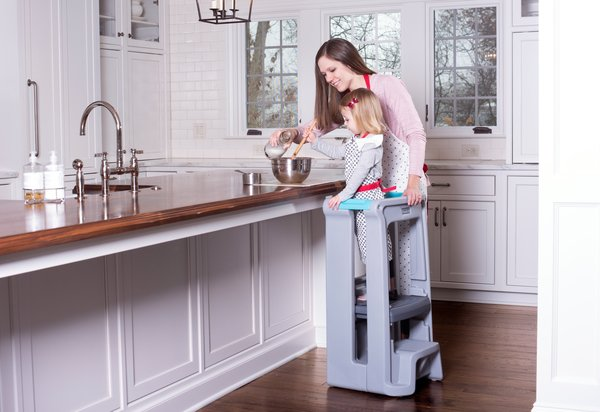 A person standing in a kitchen with a child on a stool helping put ingredients in a bowl.
