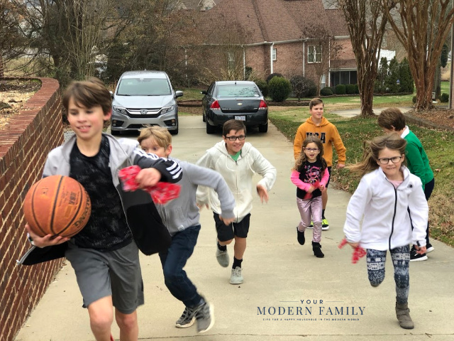 A group of kids running down the street to play basketball.