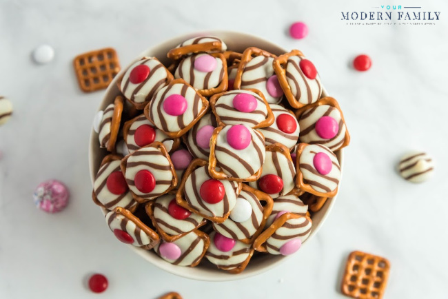 A bowl of Valentine pretzel buttons on a table.