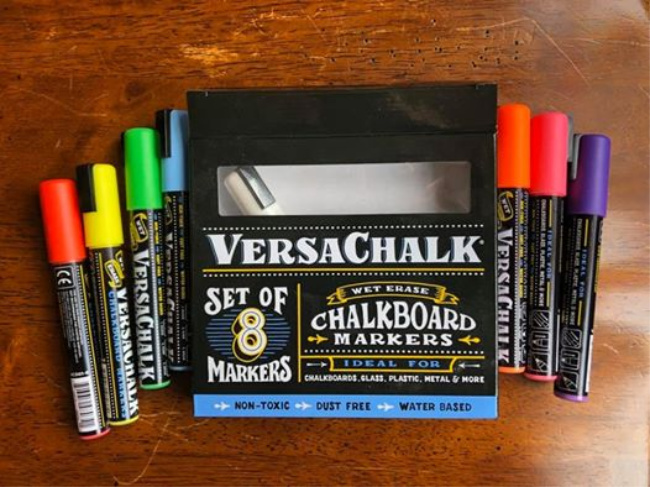 Chalkboard markers on a wooden table.