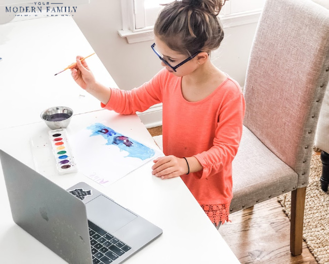 child sitting at a table using a laptop