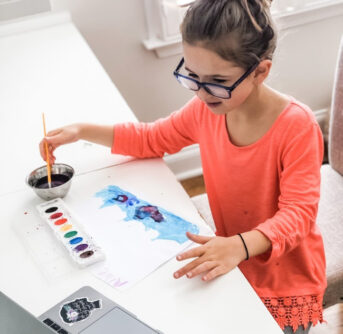 child painting sitting at a table using a laptop